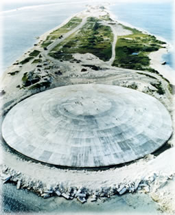 Beneath this concrete dome on Runit Island (part of Enewetak Atoll), built between 1977 and 1980 at a cost of about $239 million, lie 111,000 cubic yards (84,927 cubic meters) of radioactive soil and debris from atomic bomb tests on the Bikini and Rongelap atolls. The dome covers the 30-foot (9-meter) deep, 350-foot (107-meter) wide crater created by the May 5, 1958, Cactus test. Note the people atop the dome. Archive Photo Credit: Defense Special Weapons Agency.