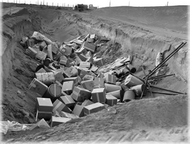 Until 1970, solid low-level and transuranic waste at the Atomic Energy Commission's nuclear weapons facilities (shown here is Hanford Reservation, circa 1950s) was frequently disposed of in cardboard boxes. Once filled, this unlined trench would have been covered with dirt, leaving the cardboard to deteriorate and allowing the waste to contaminate the soil and leach into the groundwater. Photo from the Brookings Institution archives.