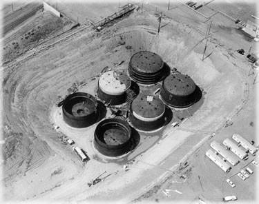 This is a tank farm under construction on the Hanford nuclear site in Washington. The principal function of the tank farms is the storage of byproduct material left over from plutonium extraction operations prior to permanent disposal. This byproduct material has no useful purpose and is stored in 177 underground storage tanks with a cumulative total capacity of 55 million gallons, with individual tanks ranging up to 1,000,000 gallons (pictured). This waste material is composed of toxic chemicals that were used to remove fission products from irradiated reactor fuel. Photo is from the Department of Energy.